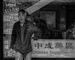 Supplements (kristenscotti) Tags: chicago chinatown china blackandwhite bw bokeh window absoluteblackandwhite chinese supplements smoking columbia jacket man old mobile highcontrast outside city urban