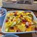 Obstsalat mit Melone, Trauben, Mango und Ananas, in einer weißen Schale mit Löffel an einem Büfett
