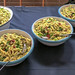 Nudelsalat mit grünen Blättern, in mehreren Schüsseln in Vintageoptik, am Essensbüfett