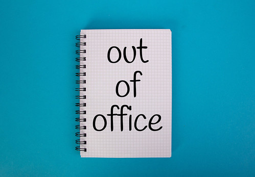 Out of office text written in notebook