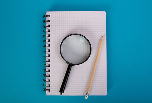 Blank notebook with pencil and magnifying glass
