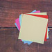 Empty colorful sticky notes on wooden background