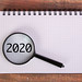 Magnifying glass over 2020 written in notebook