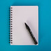 Notebook with pencil on blue background