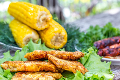 Meat chops, boiled corn and fried sausages on an old table in the yard outside (wuestenigel) Tags: boiled wooden lettuce fried table dish background meat snack fillet corn grey food leaves outside grill plate roast freshness sausages green cob yellow sirloin portion