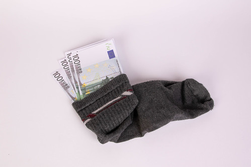 An old woolen sock full of Euro money on a white background