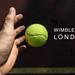 Hand wirft zum Aufschlag einen Tennisball, neben dem Namen des britischen Tennisturniers