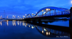 Foryd Bridge (Peter.S.Roberts) Tags: interesting forydbridge rhyl northwales thebluebridge seascape riverscape longexposure blue bluehour river water sea riverclwyd reflections reflectionsonwater night evening outdoor bridge lights lighting streetlights boat yacht mast shadows sky clouds road roadbridge pillars girders railings calm peaceful relaxing serene tranquil riverwall coast coastal details colour hightide mountain bushes trees welsh wales cymru petersroberts flickr nikond7200 wide wideangle 53321°n3480°w moorings warm june12019 deadcalm text history historic photographyvision fotografíavisión