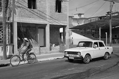 Cuban Transportation (peterkelly) Tags: digital bw northamerica cuba cubalibre gadventures canon 6d pinardelrio state town oldcar bike bicycle road street building cyclist hat hydro utility pole