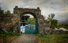 Outside of the monastery grounds (Tiigra) Tags: door fog court gate armenia 2011 sanahin loriregion mountain plant tree grass rock metal wall architecture arch village path ruin medieval laundry portal