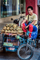 Pineapple Street Vendor (FotoGrazio) Tags: fruit streetportraiture bicycle smile waynesgrazio streetscene street people fotograzio food licenseplate travelphotography philippines bacolod tropicalfruit islander pineapple man colorful waynestevengrazio streetvendor travel transportation streetphotography filipino colors streetportrait waynegrazio visayas pacific pedicab