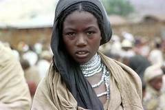 78-526 (ndpa / s. lundeen, archivist) Tags: nick dewolf color photograph photographbynickdewolf 1976 1970s film 35mm 78 reel78 africa northernafrica northeastafrica african ethiopia southernethiopia ethiopian people localpeople village unidentified woman localwoman youngwoman girl face portrait silver jewelry necklaces beads braids braided hair headcovering scarf hajib crowd
