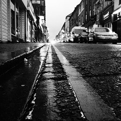 Wellington Street, Luton (Hammerhead27) Tags: road street urban blackandwhite bw monochrome lines car dark mono town vanishingpoint parking shops convergence gutter luton iphonephotos building tarmac pavement sidewalk lowpov