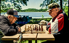Seasoned Competitors (Scott M. Mohn) Tags: men game chess competition outdoors bench shade shadows minnesota board skill summer hats quiet silence texture