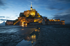 "as night falls the magnificent Mont Saint Michel and its lights are reflected in the water channels. Manche, Normandie, France (grumpybaldprof) Tags: ""montstmichel"" ""stmichael'smount"" avranches manche normandy france tidal island sea abbey ""bayeuxtapestry"" monastery ""8thcentury"" unesco ""worldheritagesite"" fortifications ""quicksand"" castle ""fineart"" striking artistic interpretation impressionist stylistic style contrast shadow bright dark black white illuminated mood moody atmosphere atmospheric calm peaceful tranquil restful ""longexposure"" night nocturne nighttime ""lowlight"" canon 70d ""canon70d"" sigma 1020 1020mm f456 ""sigma1020mmf456dchsm"" ""wideangle"" ultrawide"