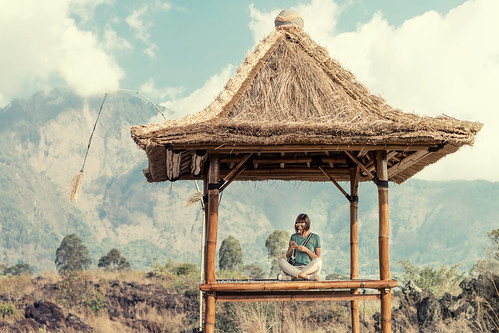 Young woman in traditional balinese gazebo.