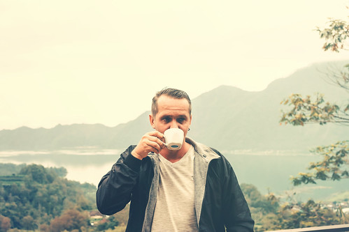 Young man traveler with white cup of coffee on a mountain background. Bali island.