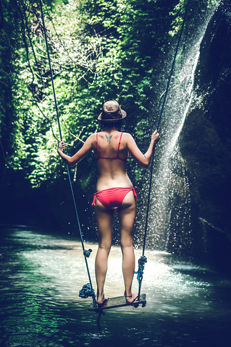 Young woman tourist with straw hat deep in the rainforest with waterfall background. Bali island.