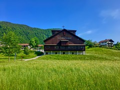 Passionsspielhaus (Passion Play Theatre) at lake Thiersee in Tyrol, Austria (UweBKK (α 77 on )) Tags: österreich tyrol tirol austria europe europa iphone passionsspielhaus passionsspiele passionplay passion play theatre house building architecture lake thiersee grass green field