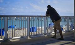 Man at Rail on Beach (LarryJay99 ) Tags: men male man guy guys dude dudes blackmale blackman rails fence horizon bluesky blue ocean atlanticocean cargos cargopants azure flipflops lines verticals beach