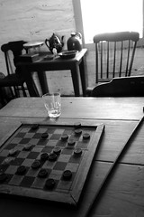The Game That Will Never End (peterkelly) Tags: digital bw northamerica canon 6d canada ontario pointpeleenationalpark delaurierhouse checkers checkerboard game table chair glass bowl crock window rockingchair