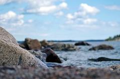 By the sea (Stefano Rugolo) Tags: stefanorugolo pentax k5 pentaxk5 tamronspaf90mmf28dimacro11 lowangle pof depthoffield pebbles clouds sky coastline island sea seashore balticsea bokeh rocks water