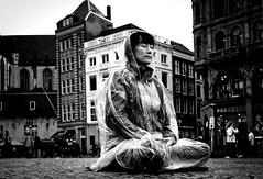 plastic spirituality (Gerrit-Jan Visser) Tags: geimporteerd streetphotography amsterdam bnw blackandwhite spirituality plastic rain damsquare meditation raincoat