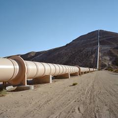 aqueduct. mojave desert, ca. 2012. (eyetwist) Tags: eyetwistkevinballuff eyetwist aqueduct pipeline water jawbonecanyon mojavedesert california mamiya 6mf 50mm kodak portra 160nc mamiya6mf kodakportra160nc mamiya75mmf35l ishootfilm ishootkodak analog analogue film emulsion mamiya6 square 6x6 mediumformat 120 primes filmexif iconla epsonv750pro lenstagger mojave desert highdesert dirt arid dry blue sky vanishing point vanishingpoint american west newtopographics infrastructure losangeles la pipe siphon canyon hillside ladwp