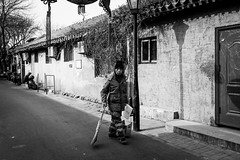 The man in charge (Go-tea 郭天) Tags: pékin républiquepopulairedechine hutong beijing ancient alley old history historical historic traditional tradition buildings brick narrow man uniform alone lonely busy duty work working walk walking clean cleaning cleaner staff broom shovel wall sun sunny shadow cold winter hat cap portrait street urban city outside outdoor people candid bw bnw black white blackwhite blackandwhite monochrome naturallight natural light asia asian china chinese canon eos 100d 24mm prime