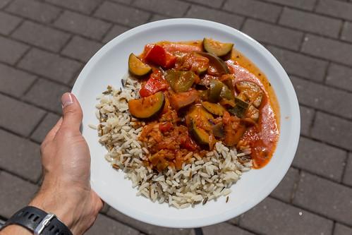 Mann zeigt veganes Ratatouille aus Zucchini, Tomaten und Zwiebeln mit Wildreis auf dem BarCamp  in Koblenz
