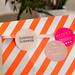 Überraschungstüte als liebevolles Geburtstagsgeschenk in einer weiß-orange-gestreiften Papiertüte mit drei runden Aufklebern