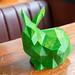 Nahaufnahme eines grünen Kaninchens auf einem Holztisch gedruckt von einem 3D Drucker