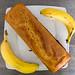 Ansicht von oben auf ein kastenförmiges Bananenbrot neben zwei ganzen Bananen