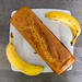 Top view of a box-shaped banana bread next to two whole bananas