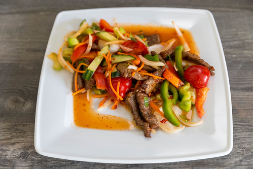 Spicy Thai food with beef, healthy vegetables, onions, carrots and fish soup on a white plate on a wooden table