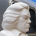 Face of white Beethoven statue in honor of the Beethoven Year 2020, in front of an old camping van