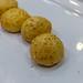 Runde Käsebällchen mit Schinkenfüllung auf einem weißen Teller