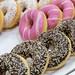 Bunte Donuts mit weißer und pinker Glasur, mit Schokoguss und bunten Streuseln