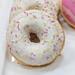 Nahaufnahme zeigt Donuts mit Zuckerguss und bunten Streuseln