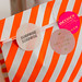 Surprise bag as a loving birthday gift in a white-orange striped paper bag with three round stickers
