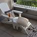 Weißer Liegestuhl mit gemütlichen Kissen, Sommerschlappen und Sonnenmilch, auf einem Balkon