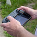 Männerhände steuern eine Drohne mit der Man operates a DJI Mavic 2 Smart Controller Fernbedienung im offenen Gelände