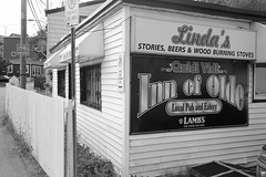 Stories, Beers & Wood Burning Stoves (peterkelly) Tags: digital bw northamerica canon 6d canada stjohns newfoundlandlabrador quidividi innofolde shop store window fence stories beers lindas woodburningstoves pub eatery awning sign