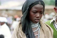 78-527 (ndpa / s. lundeen, archivist) Tags: nick dewolf color photograph photographbynickdewolf 1976 1970s film 35mm 78 reel78 africa northernafrica northeastafrica african ethiopia southernethiopia ethiopian people localpeople village unidentified woman localwoman youngwoman girl face portrait silver jewelry necklaces beads braids braided hair headcovering scarf crowd hijab fly flyonherface