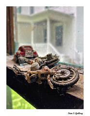 Long ago abandoned toys resting on the barn window (Stan S. Gallery) Tags: tire debris dust forgotten toys window motorcyccle car porch abandoned lost resting old wheel paneofglass