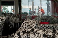 Circles (Glass Eye Chromatic) Tags: thessaloniki perea greece september 2014 cafe seats mirrors pattern circles woman cyclist man panasonic lumix gx7 olympus17mmf18