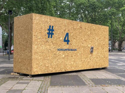 Konsumfreiraum-Kunstwerk aus Sperrholz kritisiert Konsumgesellschaft an der Schildergasse in Köln, während des Kunstfestivals Impulse Theater Festival