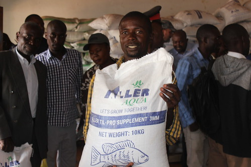 Smallholder fish farmer Royd Mwamba holds up a bag of fish feed at the opening of Horizon Aquaculture's Kasama outlet, Northern Province, Zambia. Photo by Tabitha Mulilo.
