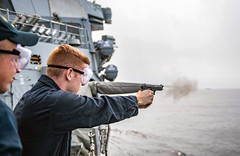 """A Sailor shoots a 9 mm pistol USS Curtis Wilbur (DDG 54) during a live-fire exercise (#PACOM) Tags: usscurtiswilburddg54 underway livefireexercise eastchinasea usindopacificcommand """"usindopacom"""