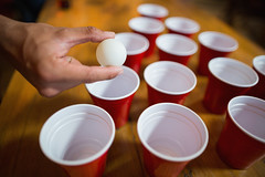 Cropped hand of man playing beer pong (republicbarmarketing) Tags: partof humanhand playing beerpong bar focusshot humanbodypart humanfinger lifestyle enjoyment game table restaurant ball disposablecup having holding pub hipster glass leisure casual fun party amusement joy pleasure amusing entertaining celebration red pingpong white brown shape unhealthy standing smiling together friendship togetherness shouting mouthopen blurredmotion millennial